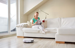 Happy woman and robot vacuum cleaner at home Royalty Free Stock Image