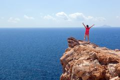Happy woman on the rock with hands up. Winner, success, travel. Stock Image