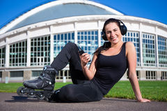 Happy woman in roller skates sitting and listening music Royalty Free Stock Photos