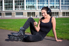 Happy woman in roller skates sitting and listening music in park Royalty Free Stock Photography