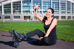Happy woman in roller skates sitting and making selfie photo on Stock Images
