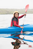 Happy woman rowing on lake Stock Photography
