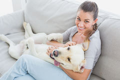 Happy woman rubbing her yellow labrador on the couch Royalty Free Stock Photos