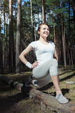Happy woman runner doing workout stretching out outdoors in forest. Royalty Free Stock Image