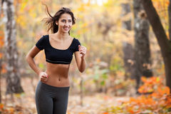 Happy woman running in autumn forest Royalty Free Stock Photos