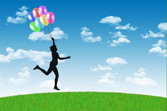 Happy woman running with balloons on a blue sky background Stock Image