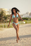 Happy woman running on the beach. Image of a happy black woman running on the beach stock photo