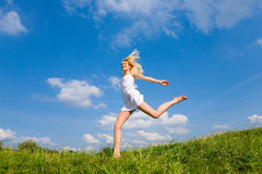 Happy woman is running on a field. Against the backdrop of blue sky Stock Images