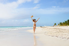 Happy woman running and having fun on tropical beach vacation Stock Image