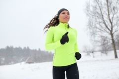 Happy woman running outdoors in winter Stock Photo