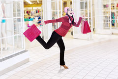 Happy woman running in shopping center Stock Photos