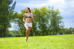 Happy Woman running on summer or spring grass field Royalty Free Stock Photos