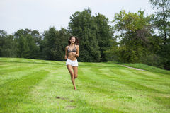 Happy Woman running on summer or spring grass field Stock Photos