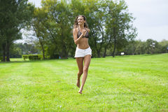 Happy Woman running on summer or spring grass field Stock Image