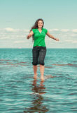 Happy woman running on the water of sea Stock Photo