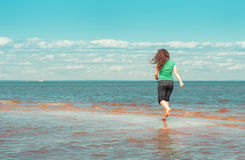Happy woman running on the water of sea Stock Image