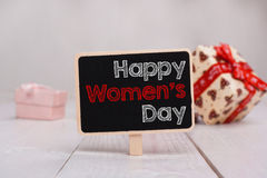 Happy Woman's Day message written on little chalkboar. Backgroun. D with gifts Stock Photos