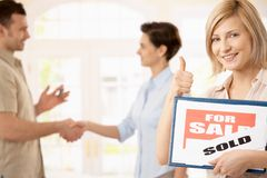 Happy woman with for sale sign. Happy woman holding for sale sign giving the thumb up, smiling man shaking hands with estate agent in background Royalty Free Stock Photos