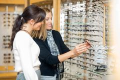 Happy Woman With Salesgirl Examining Eyeglasses. Happy women with salesgirl examining eyeglasses in optician store Stock Photography