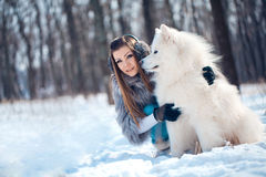 Happy woman with Samoyed dog in winter forest Stock Photography