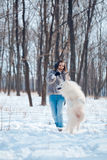 Happy woman with Samoyed dog in winter forest Stock Photos