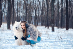 Happy woman with Samoyed dog in winter forest Royalty Free Stock Image
