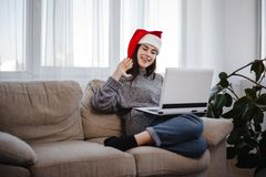 Woman waving during video call sitting on a couch stock photography
