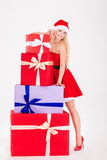 Happy woman in santa cloth standing with gift boxes Stock Photo