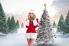 Happy woman in santa costume standing against digitally generated background Royalty Free Stock Images