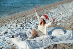 Happy woman in santa hat celebrates 2021 on the beach with snow.