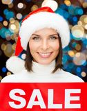 Happy woman in santa hat with christmas sale sign Stock Photo