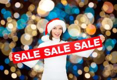 Happy woman in santa hat with christmas sale sign Stock Photography