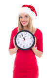 Happy woman in santa hat with clock posing isolated on white Royalty Free Stock Images
