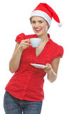 Happy woman in Santa hat drinking hot beverage Stock Photos