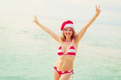 Happy woman in Santa hat enjoying winter vacation on the beach royalty free stock images