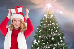 Happy woman in santa hat holding christmas gift on her head Stock Photography