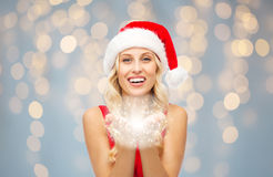 Happy woman in santa hat holding fairy dust Royalty Free Stock Images