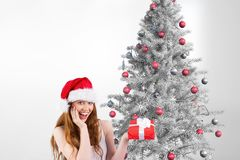 Happy woman in santa hat holding a gift against christmas background. Portrait of excited woman in santa hat holding a gift against christmas background Royalty Free Stock Images