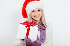 Happy woman in santa hat holding gift box. Over white Royalty Free Stock Images