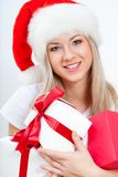 Happy woman in santa hat holding gift boxes. Over white Royalty Free Stock Images
