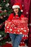 Happy woman holding many Christmas gifts royalty free stock photo