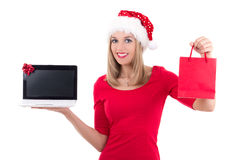 Happy woman in santa hat holding notebook and present over white Royalty Free Stock Images