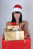 Happy woman in santa hat holding presents Stock Photo