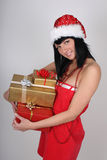 Happy woman in santa hat holding presents Royalty Free Stock Photo