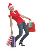 Happy woman in Santa hat holding shopping bags Royalty Free Stock Image
