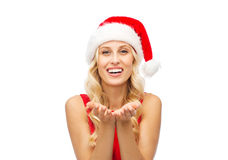 Happy woman in santa hat holding something on palm Royalty Free Stock Photo