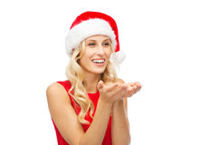 Happy woman in santa hat holding something on palm Royalty Free Stock Image