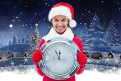 Happy woman in santa hat holding a wall clock Royalty Free Stock Images