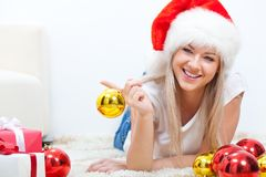 Happy woman in santa hat laying on carpet Stock Images