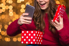 Happy woman in santa hat opened present and got smartphone Stock Photography